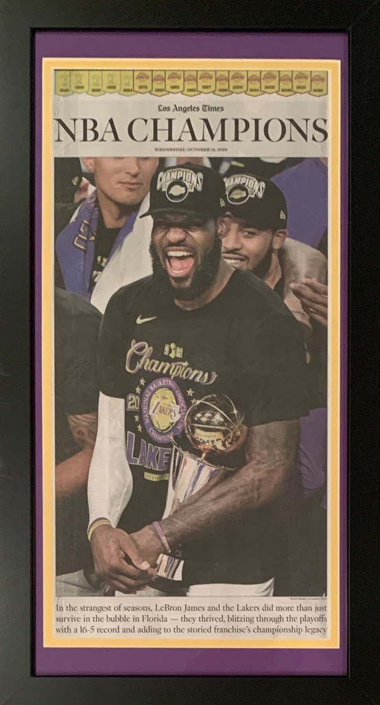 "Los Angeles Lakers 2020 NBA Champions Times Original Basketball Framed Newspaper LeBron James 10/14/20 This is the original framed special edition section of the 2020 Los Angeles Times from the day after the Lakers won the 2020 NBA Championship.  LeBron James's 1st with the Lakers.  Comes framed in Lakers colors as shown. Black frame measuring 14x26."" Easily one of the best gifts you can give to a Lakers fan. Looks stunning hanging up on a wall in an office or man cave.  Especially with LeBron James on the cover."